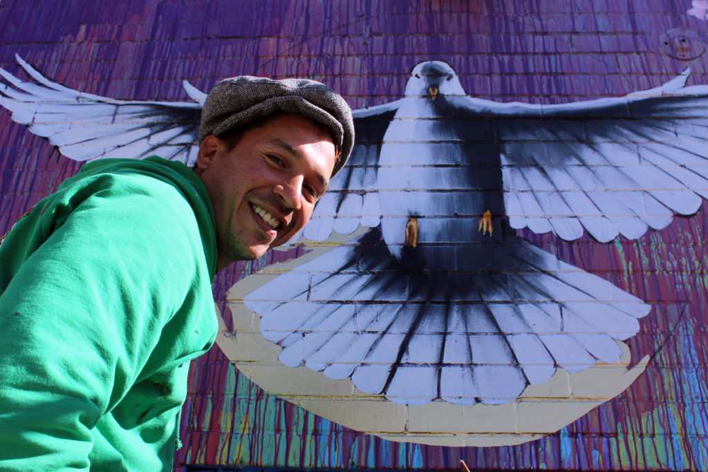 Artist Luis Valle with the dove painted at Local 46-a symbol of grace and peace.