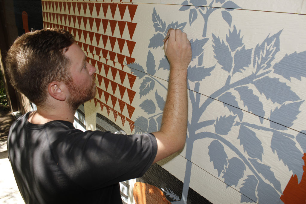 Bond paints details on leaves of potato plant in a nod to Woody Creek Distillery branding.