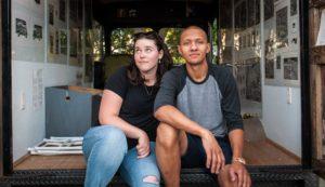 Corianne & Kristopher sit outside 'Grafico Movil', a multi-community collaborative art project